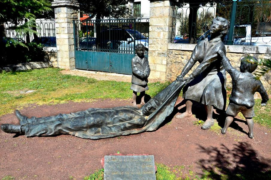 "The sculpture entitled ""NO MORE WARS,"" by sculptor Nikos Dimopoulos, is in the courtyard of the Museum of the Kalavritan Holocaust. It was donated by the family of Andrew Varelopoulos. It represents a woman who is dragging her executed husband while her c"